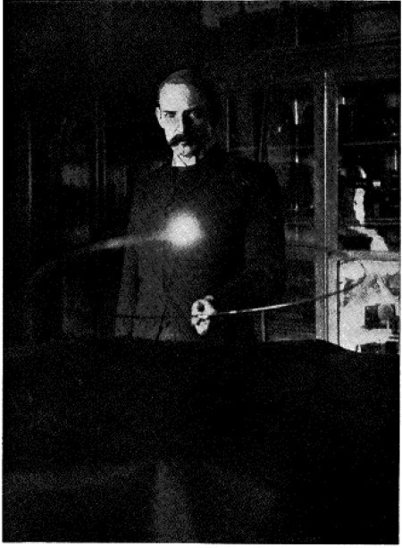 Fig. 11. — Experiment illustrating the lighting of an incandescent lamp in free space by induction from coil below, energized by distant circuit around the room. The loop of wire carrying the lamp is held by Mr. Marion Crawford. (From flash-light photo)
