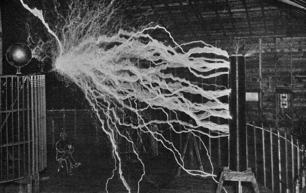 Fig. 3. — Compare the Size of the Tesla Coils Here Shown with That of the Man at the Left. A Double Exposure Was Necessary — First with the Man and Apparatus, Then with the Apparatus (Less the Man) Fully Excited. Sparks Measure 22 Feet in Lengt