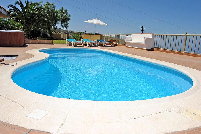 Pool mit Sonnenliegen und Meerblick.