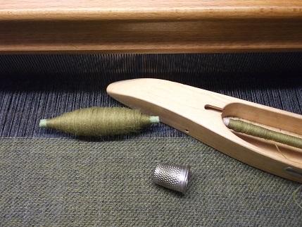 Detailbild Stoff am Webstuhl der Fingerhut dient dem größenvergleich