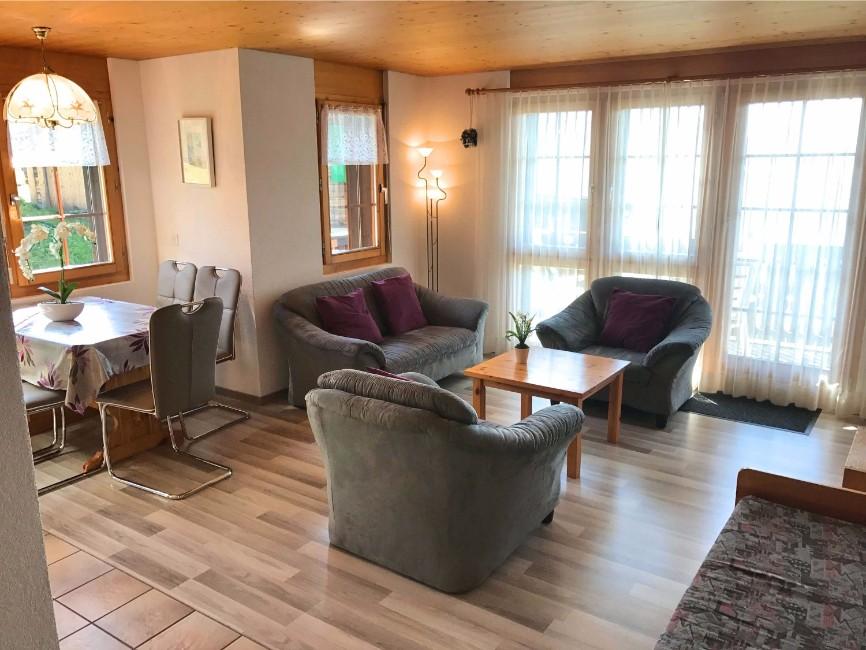 Wohnzimmeransicht mit Sofa und TV in der Sonnenhalde C12 auf der  Riederalp