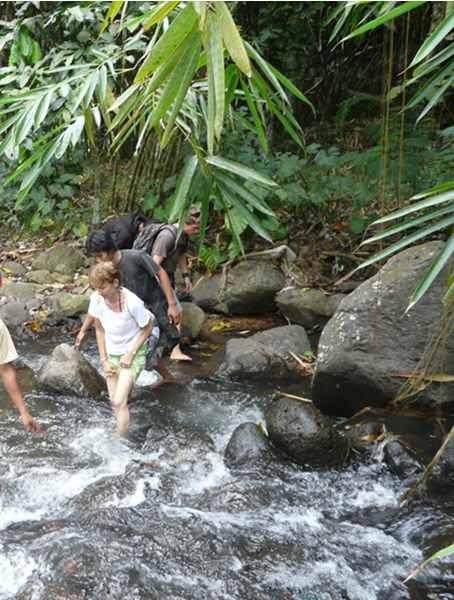 Vorsichtig tasten sich Touristen durch einen lebhaften Bergbach