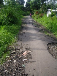 Nebenstraße mit teilweise zerstörtem Straßenbelag