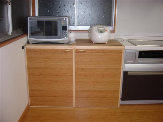 システムキッチン横のスペースには床板を利用して扉を作ったオリジナル棚を。