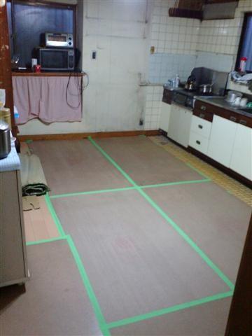 台所床張りがほぼ完了、傷が付かない様に保護しておきます、奥に見えるキッチンをシステムキッチンに変えます。