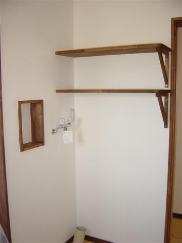 洗面脱衣室、窓の反対を振り返ると洗濯機や木製の戸棚があります。