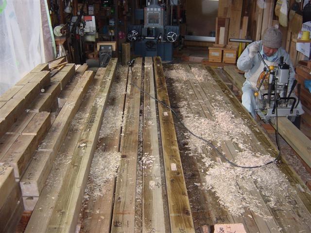 土台きざみ作業中、柱のホゾが入る穴を掘っています。