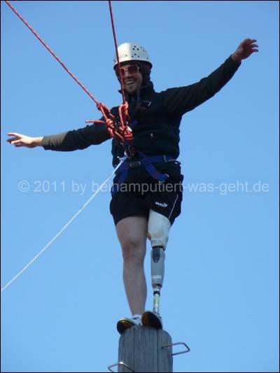 Mann steht mit Prothese auf einem Stamm im Kletterpark