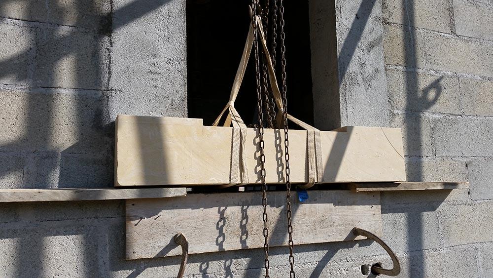 Construction des écuries du château, pose d'un appui de fenêtre en pierre