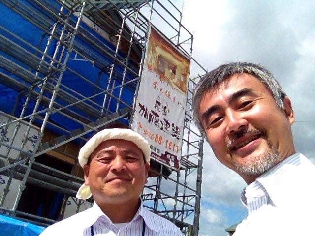 建築現場の垂れ幕の前で、豊橋の日本家屋を建ててる棟梁と