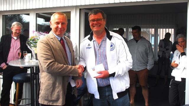 Amtsvorsteher Jörg Engelmann übergibt 1. Vorsitzenden  Holger Fockenga das Präsent des Amtes