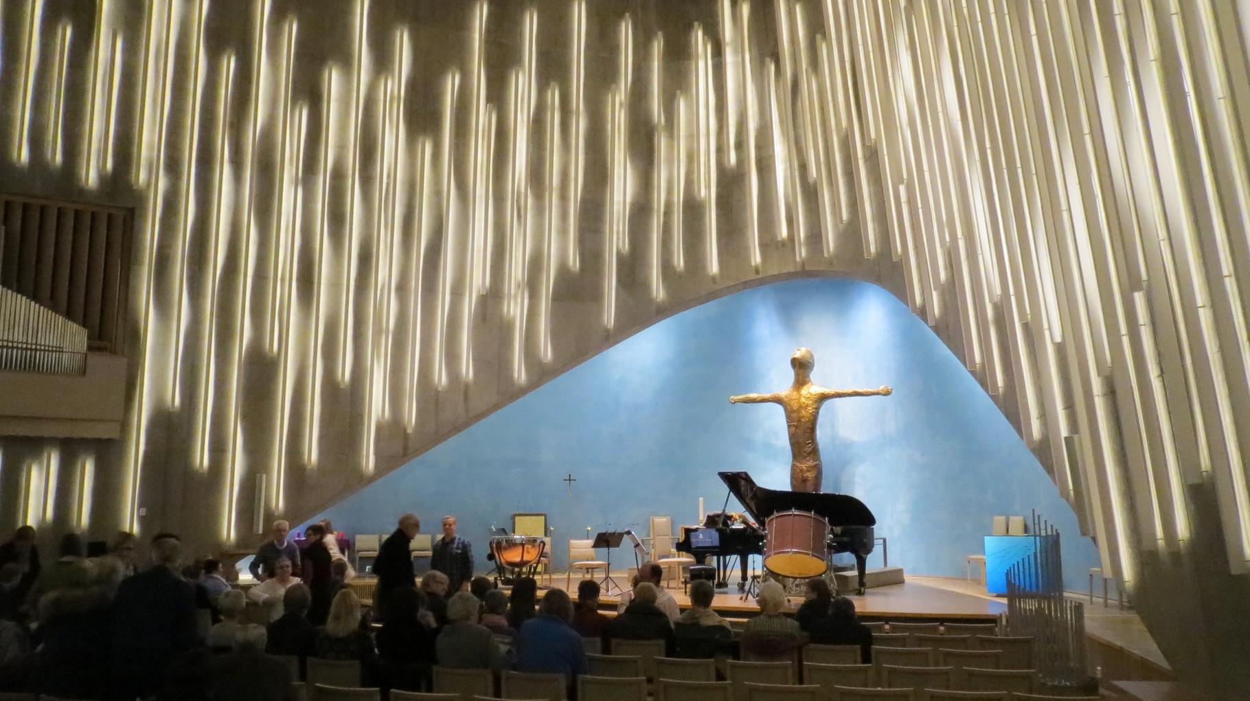 Riesiger Bronzechristus, die Wand von Altas Kindergarten blau gemalt und Nordlichtlampen an der Wand ...