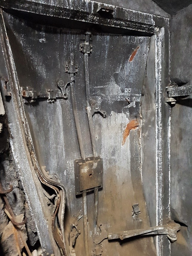 De bewapende deuren van enkele tonnen metaal en beton staan nog steeds als een blaadje krom geblazen ettelijke meters als getuigen van deze operatie verder tegen een muur aan.