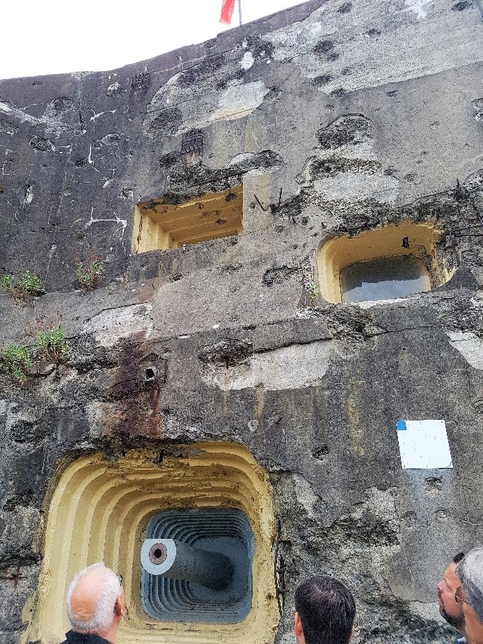 Bij de ingang zelf staan geschutskoepels de gasten op te wachten. Rondom de dikke grijze betonnen bunkermuren zien we nog de kogelinslagen en granaatscherfinslagen. Duidelijk dat hier hard gevochten was.