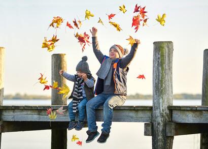 Kinder sitzen auf einem Steg und werfen Laub in die Luft