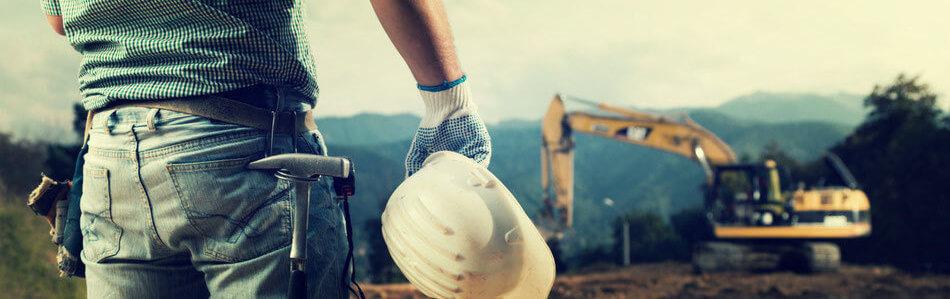 Mann auf einer Baustelle, der mit seiner Versicherung sicher durchs Leben geht