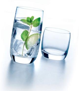 Twee waterglazen. Eén is gevuld met ijs, water, munt en limoen.
