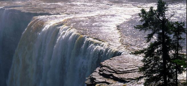 De bovenkant van een grote waterval waar je het water naar beneden ziet vallen