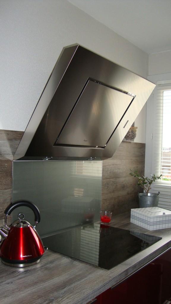 cuisine design rouge avec son linèaire cuisson et sa hotte inclinée