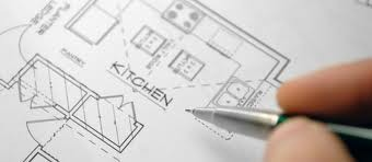 Close up of hand holding a pen over a blueprint drawing of a kitchen.