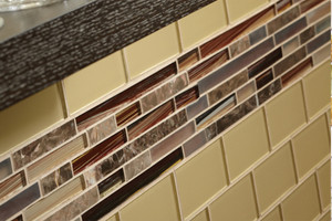 "Close-up shot of a kitchen backsplash with yellow 3x6"" glass tile and a horizontal stripe of red and brown glass and marble linear mosaic."