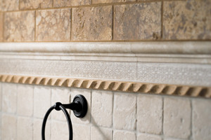 Travertine bathroom wall with decorative borders