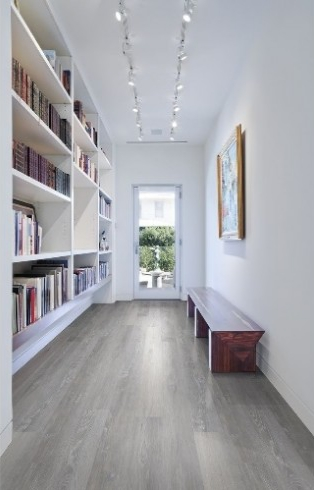 Entryway with light taupe gray lvt flooring that looks like wood. White walls and bookcases
