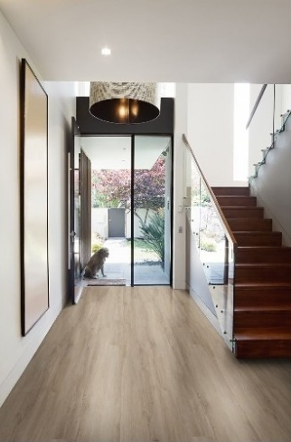 Entryway with luxury vinyl tile that looks like light hardwood. There's a red staircase and a dog sitting in the open front doorway