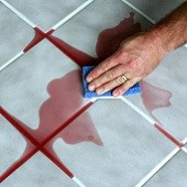 Hand wiping spilled wine off of tile floor
