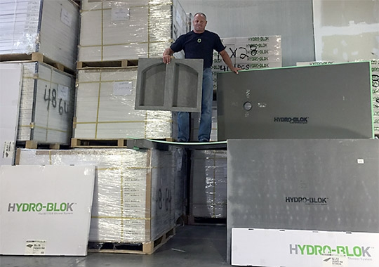 Hydro Blok US distributor Brian Wright stands on a piece of Hydro Blok Wall Board.