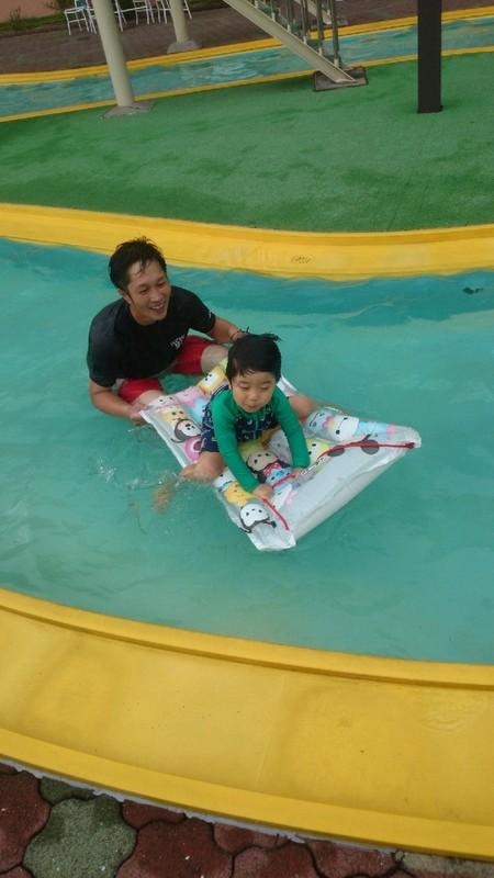 ホテルのプールで泳ぐ社長と子供の写真