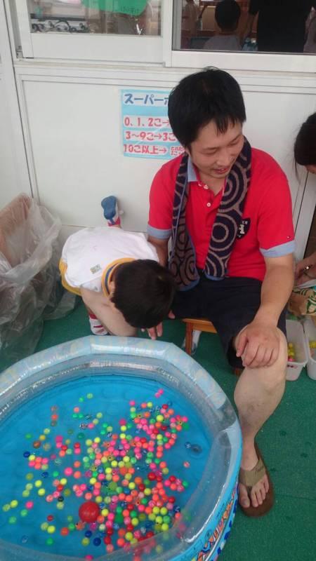 休日子供のバザーに参加する社長の写真