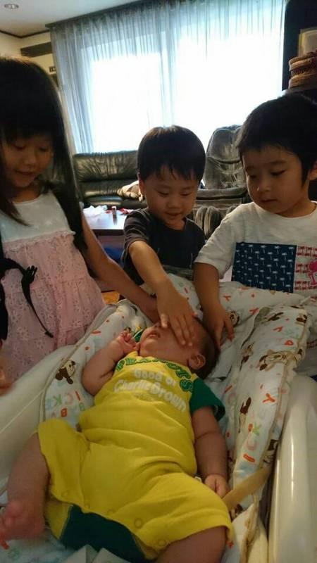 みんなに触られる赤ちゃんの写真