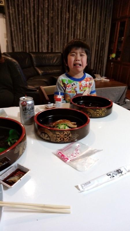 お寿司を前に泣いている子供の写真