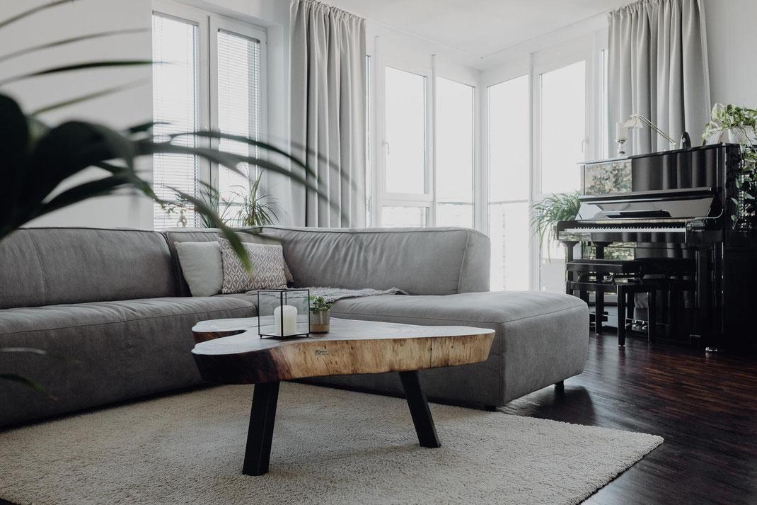 Lichtdurchflutetes Zimmer mit Industrial Möbel - Tisch, Teppich, Designer Couch & ein Klavier
