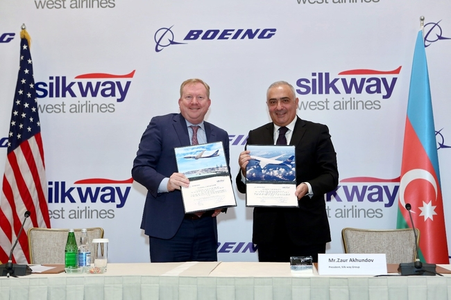 Signing mission accomplished: Zaur Akhundov, Silk Way Group (standing right), and Stan Deal, Boeing Commercial Airplanes – photo: Courtesy Silk Way West