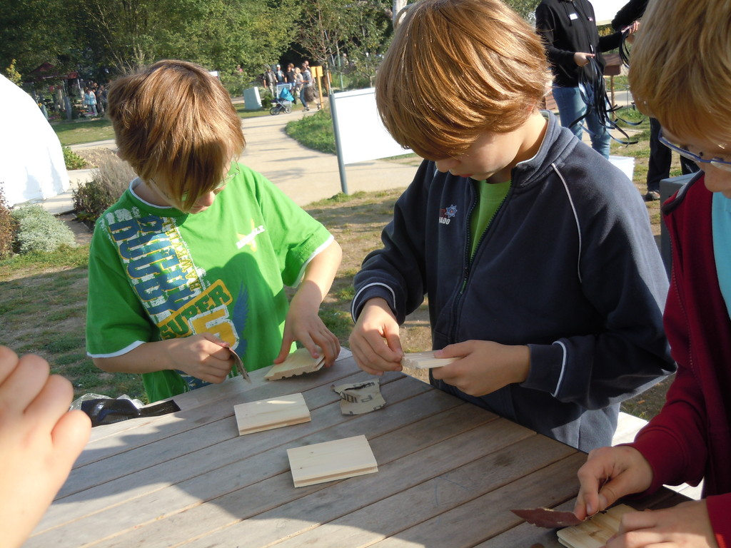 Als erstes bekommt jeder zwei kleine Holzbrettchen und ein Stück Schmirgelpapier...