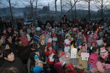 Kinder und Eltern warten gespannt auf den Beginn des Laternenumzugs.