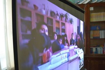 Schueler der Klasse 10 der 3. Oberschule in Gyumri (Armenien) blicken gespannt auf den Bildschirm und sprechen mit unseren Schuelern.