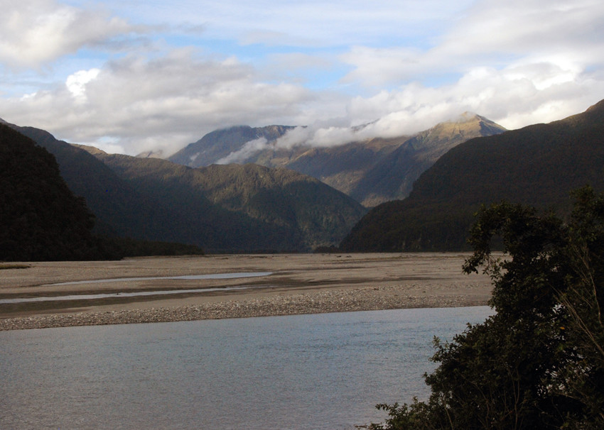 The broad braided river bed of the Haast beyond the Haast/Landsborough confluence. The steep thickly wooded hills rising up to Mt Awkward, Hassing Peak (2088m) and Mt Maitland (2270m).