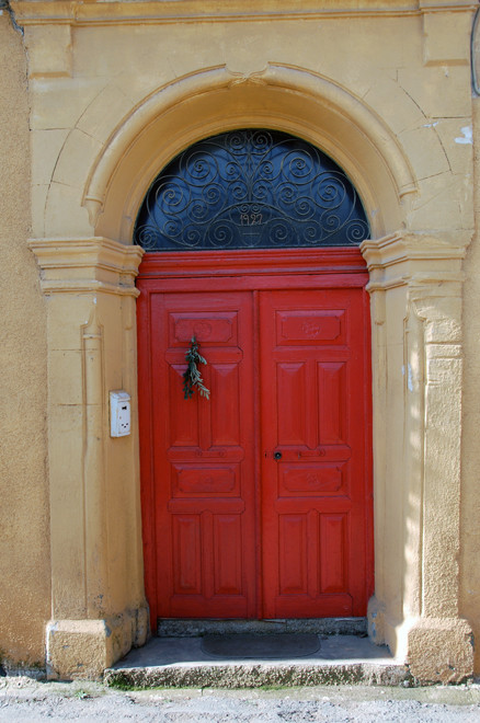 Arched, sandstone doorway with scrolled ironwork dated 1927, Peristerona