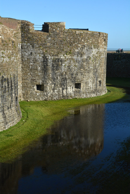 Reflections in the deep, dark blue of Deal castle moat.