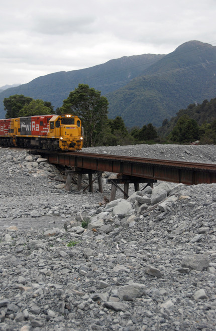 The double-engined Kiwi Rail diesel train pulling up the Otira Valley at the desert-like Kelly's Creek
