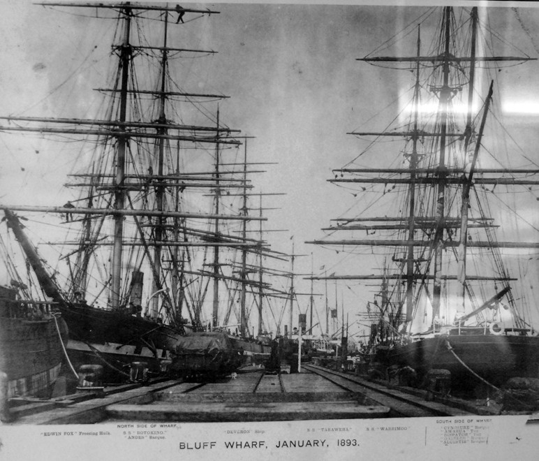 Sailing ships tied up to the Bluff Wharf in 1893. Two foremost ships (L) SS Rotokino and (R) SS Warimoo plus 4 barques, 2 tugs, 1 ship and 1 freezing hulk (from South Sea Hotel, Stewart Island).