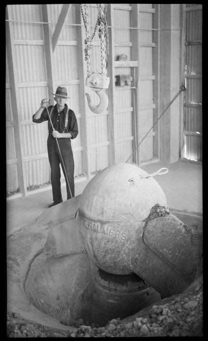A worker beside pulley hook and grinder inside the Golden Bay Cement Works, Tarakohe. Photograph taken circa 1939, by Thelma Rene Kent.(Click for source)