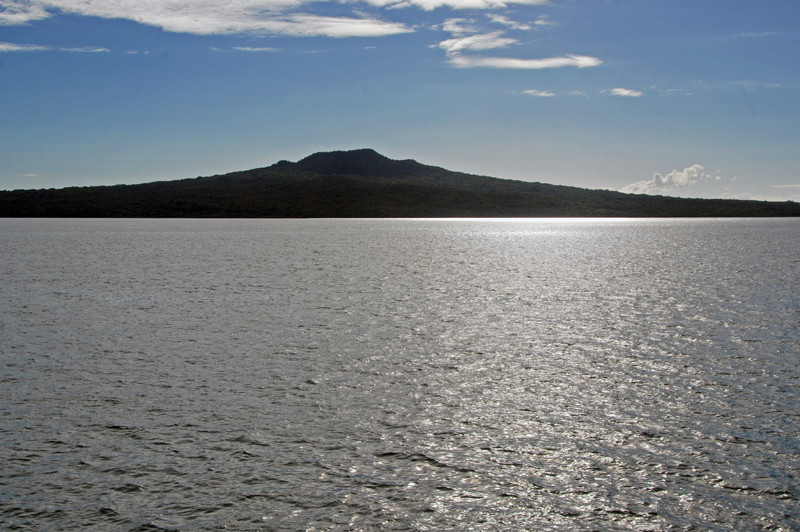 The distinctive shield cone-shaped silhouette of volcanic Rangitoto Island rising to 850 ft. The island was formed only 550-600 years ago.