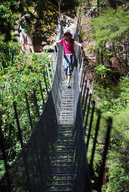 Karen takes on the swing bridge over the Wainui River in Golden Bay.