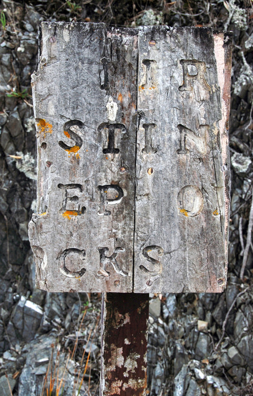 An old weathered sign I eventually deciphered - Birds Nesting: Keep Off Rocks.