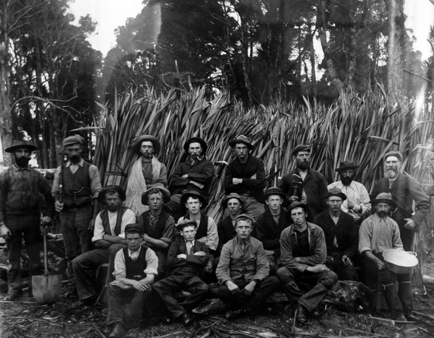 Flax mill workers in Mangakarau - flax sheaves in background and man third from left festooned in shank of processed flax (c. 1890s Tyree Studio - Photo of photo in Community Centre)