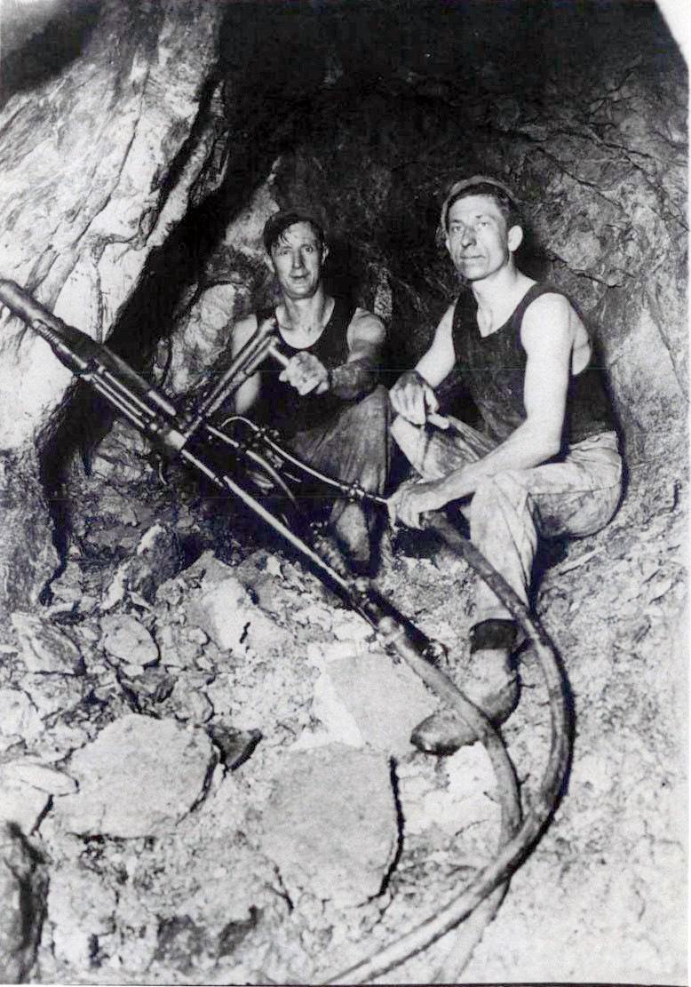 Bill Horton (right) and Tom Dobson drilling charge holes in a Waiuta gold mine in the 1930s (Joe Divis, Hocken Collection). Note the The black singlets which have 'come to symbolise the male New Zealand rural' (Te Ara).